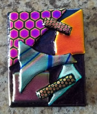 abstract pin or pendant handcrafted in dichroic glass in the USA